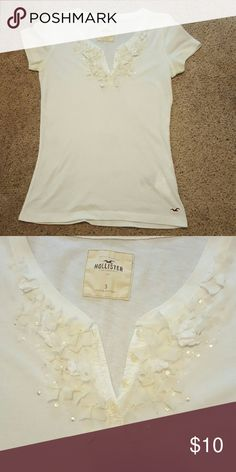 Embellished Hollister tshirt White embellished Hollister tshirt...white and cream embellishments around neckline very girly and sweet! Sz small. Hollister Tops Tees - Short Sleeve
