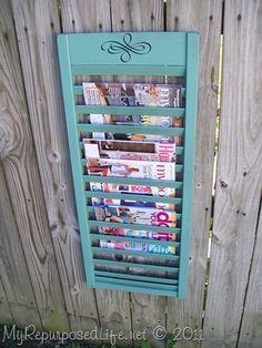 magazine rack from an old shutter .. so cute :) .. Note - probably not a good idea to hand it on a fence outside .. lol