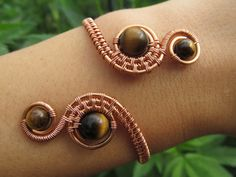 A beautiful hand-wrapped copper wire bracelet with 4 tigers eye beads and my signature spirals.    Tigers Eye is a natural stone that