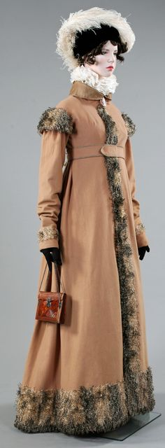 "Aglae. From the exhibition ""Napoleon and the Empire of Fashion"". Lancaster-Barreto collection.Coat: Camel wool in natural colour. Silk organza collar, pipping and buttons. Pluche de some, imitating fur, France, circa 1808. Mechlin collar lace.  Great example of the influence of Napoleon's peninsular war, the troubadour painting and the romanticism.  ""Manches a la espagnole""  Cameo: seashell, enamel, gold. France, first quart of the XIX century. Bag: Marrocain leather, France, circa 1804."