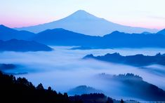 Distant view of Mount Fuji silhouetted against an blue sky