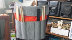 I made this drum stick bag for my husband. It is loosely based on this pattern: http://www.ehow.com/how_8486107_make-drum-stick-bag.html And also draws from RollItUp brand bags. It ties to a chair (as shown), but also can hang on the wall or a floor tom, and it can roll up for travel. I used orange flannel and orange thread, and the outside is something soft I found on the discount rack. :)