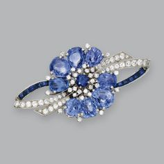 PLATINUM, SAPPHIRE AND DIAMOND BROOCH, OSCAR HEYMAN & BROTHERS, J.E. CALDWELL & CO., 1948. Designed as a stylized flower set with pear-shaped, round and calibré-cut sapphires weighing 29.97 carats, and round and single-cut diamonds weighing 2.48 carats, signed J.E. Caldwell & Co., numbered S3810. #DiamondBrooches