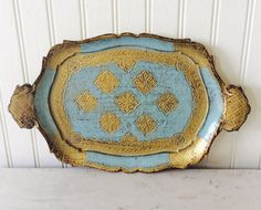 What a beautiful vintage wood tray with ornate design. This is a gold & blue decorative tray with handles . Stamped on back Made in ITALY, FLORENCE, sold at shop in Florida. In excellent vintage condition! Great for table top decor, bookshelf, vanity, bedroom, kitchen, or wall decor. Brass clamshell trinket box sold separately in shop.  Measures 12.25 x 7.5 total Thanks for shopping YellowHouseDecor