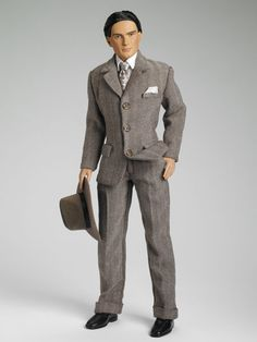"James Collins | Tonner Doll Company--  •Dressed Doll   •Face Includes Hand Painted Details   •Fine Quality Vinyl and Hard Plastic   •James Collins Head Sculpt   •17"" Matt O'Neill™ Body   •Brown Painted Eyes   •Raven Rooted Saran Hair   •Matt Skin Tone   •Tailored Suit   •Oxford Shirt   •Printed Tie   •Socks   •Molded shoes   •Hat   •Stand   •LE 500"