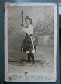"PLAY - 1900s:  Baseball Girl with bat.  Her hands were apart, a common bat grip during the times. There were teams, but no young girls baseball leagues. Older girls, called ""Bloomers,"" formed teams that barnstormed the country. It was a young lady who was responsible for the popular song, ""Take Me Out to the Ballgame."" 