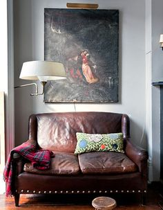 so cozyyyy!  +worn leather couch +swing-arm lamp +museum art light +color in textiles
