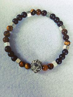 Bracelet homme fait main, composé de perles en pierres naturelles onyx mat, de perles en oeil de tigre, dun charms tête de lion, et de perles en métaux (sans nickel) à strass. Le bracelet est élastique et mesure 7cm de diamètre. Envoyé avec un emballage pret à offrir. FRAIS DE PORT OFFERT