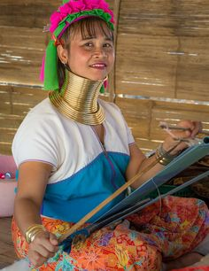 Ban Mae Khao Tom, Chiang Rai Province, Thailand. A Padaung Karen woman works at a loom. Padaung women produce beautiful fabrics and clothes made from them.