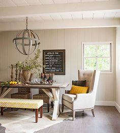 A mix of chairs and an upholstered bench surround a farm-style table for a casual look. A hide rug gives the space texture, and plank walls in a warm taupe add character. Above the table, a light fixture made from old wine ba