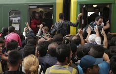 Traumatising: A young child cries as hundreds of migrants try to board a train at the Kele...