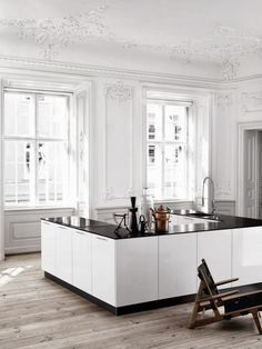 An L-shaped kitchen by Danish kitchen designer Kviks is placed in the middle of a large ornate Danish apartment | Remodelista