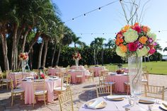 Outdoor St Petersburg Wedding Reception Décor with Gold Chiavari Chairs, Pink Linens and Orange, Bright Pink and Fuchsia Tall Floral Centerpieces with Lanterns and Market Twinkle Lights | Exquisite Events Wedding Planning