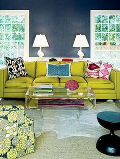 Navy on the walls could go serious, but the citrine sofa, punches of pink and lucite table make the room feel youthful and vibrant