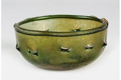 A Roman Glass Bowl, 1st century AD, possibly made in Germany, the bowl of green glass with dimples around the exterior rim, 8cm diameter