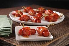 Mini smoked sausages wrapped in bacon and drizzled with sweet chili or sweet-sour sauce before baking 12 min.