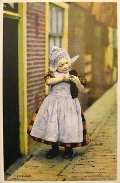 Een Volendammer meisje in dracht met jong poesje poserend op straat. 1920-1931 #NoordHolland #Volendam