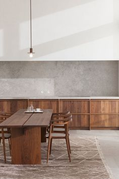 Walnut coloured dining room with stone wall and a massive wooden table.
