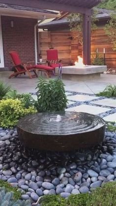 Modern Backyard Stone Water Feature and Concrete Fire Pit . The small river rock surround makes this water feature. http://www.milehighlandscaping.com/en/WATER_FEATURES.html