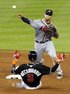 Atlanta Braves second baseman Tommy La Stella tags out Miami Marlins' Adeiny Hechavarria while turning a double play catcher Marlins' Jeff Baker in the fifth inning of a baseball game.