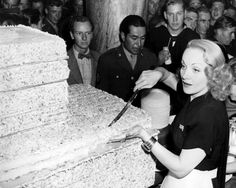 Actress Marlene Dietrich cuts an immense Birthday cake for service men (1943)