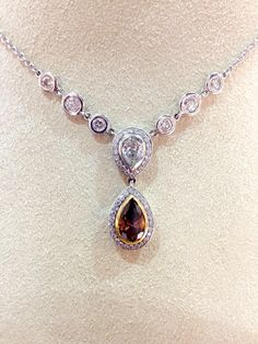 18k white gold necklace with pear shape white and cognac diamonds. 3.42 cts total weight.