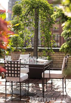 A glass-topped dining table topped with a topiary provides a delightful outdoor dining experience. - Traditional Home ® / Photo: John Bessler