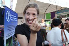 Larissa Bruun, a former UN Volunteer in Lao PDR, shows an edible insect in Vientiane, where the Food and Agriculture Organization informs the general public about its initiatives to fight malnutrition through an edible insect campaign. (Charlotte Spinazze, 2010)