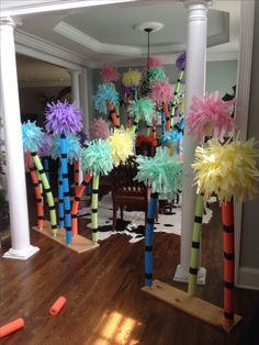 Dr Seuss trufula trees. Pool noodles + tissue paper from dollar store. Hot glued tissue flowers on top of noodle. Black duct tape for rings