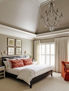 love the tan walls, white trim, tan tray ceiling.  wood shutters on windows. long neutral drapes. light fixture! (replace fan). and sconces above headboard. replace red elements with blues, greens, tan. master bedroom.