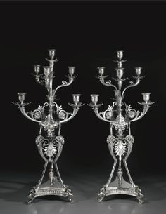 A pair of Victorian silver seven-light silver candelabra, Elkington & Co, Birmingham, 1874 heavily cast and chased, triform bases rising to ram's head terminals, incorporating anthemion, foliate swags and masks 83cm, 32 1/2 in high 15303gr, 492oz 1dwt