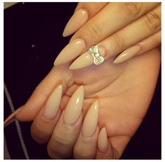 Beige nude stiletto nails with diamond bow 3d bows.