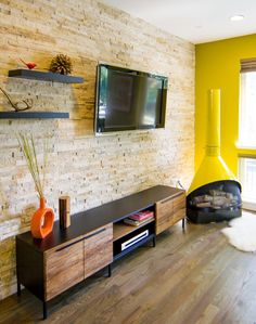 beautiful wooden flooring, exposed brick, love the tv and shelving, and that media stand