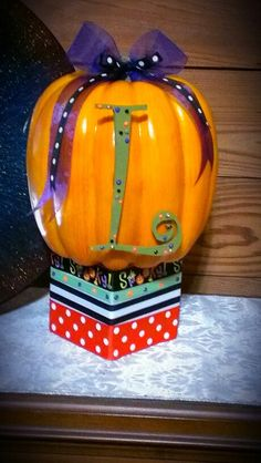 I purchased a foam block from the Dollar Tree, wrapped it with different ribbon remnants I had, hot glued a pumpkin to the top. On the pumpkin I hot glued a wooden letter I previously decorated with puff paint. I added two more ribbons formed into bows on top. Use your own initials and decorate in your own style. Have fun, be creative and then share your creations with us!