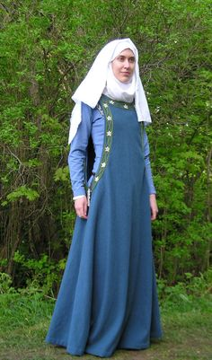 Medieval female costume, 13th century. Under: white linen shift and blue linen gown (cotehardie?); top: sideless blue woollen surcoat with embroidered trim (beads, not period). Headgear: veil and wimple