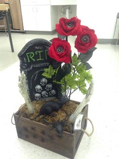 Halloween arrangement of tombstone with skeleton arms reaching out of the grave with a rat and spiders with eyeballs in roses.