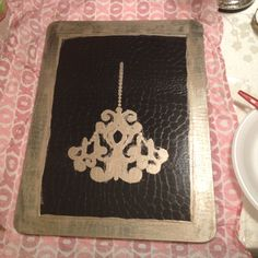"""A """"hard"""" placemat from hobby lobby, on sale for 1.50, a chandelier stencil $2.00 and some acrylic paint .87... Super easy and inexpensive!!! Great wall hanging :)"""