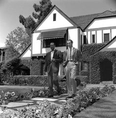 Henry Fonda and Jimmy Stewart walking down the path of Stewart's home, 1951, Los Angeles.  The new owners tore down both the house and the rose gardens and replaced them with a nondescript mansion.