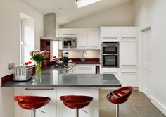 Red Sorrento Bar Stools in light white kitchen with small breakfast bar and matching red spashback