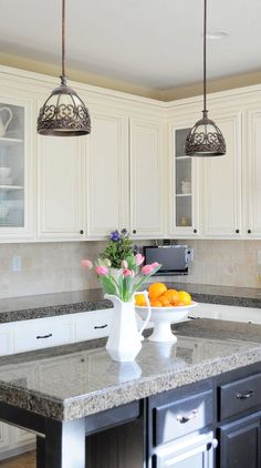 Painting cabinets has to be a whole lot cheaper than refacing.  This blog gives step-by-step instructions on painting, adding glass to doors, and staggering cabinet height.