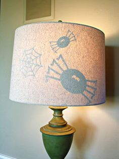 Use a vinyl cutter to create some creepy shapes (blogger Sarah went for a spider theme), and adhere them to the inside of a lamp shade.