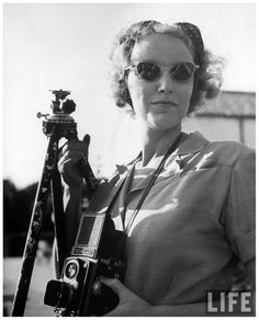 Photographer Nina Leen holding onto her Rolleiflex around neck & holding up tripod in other hand, outside 1945