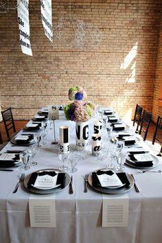 Black & white table setting against exposed brick