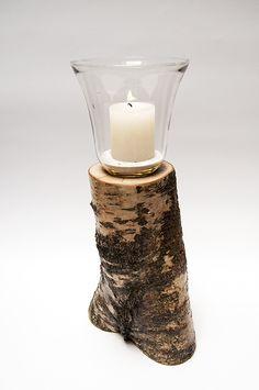 Windlicht van +/- 15 centimeter hoog met kleine stompkaars. Dit windlicht is verzonken in een berkenhouten stam met schors - gelakt.  'Authentieke, handgemaakte interieurstukken voor huis en tuin. H.T.I. Hermans Thijs'