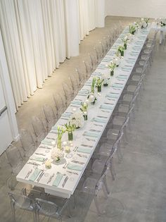 Ghost chairs, displayed in long hall style dining. These would be paired with the long white tables, with Carrera Marble tops. We suggest different flowers and glassware.