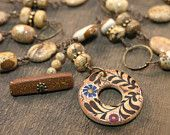animal lovers hand engraved paw print river rock pendant necklace on a copper chain. $20.00, via Etsy.