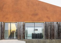 Varatojo House by Atelier Data is near the city of Torres Vedras, Portugal. The building, clad in copper-coloured cement and cork, is built around a sunken wildflower garden. A row of recycled railway sleepers border the property, which can slide open to reveal the ground floor, or slide shut to hide the windows and entrance. An indoor swimming pool looks straight through the house, across to the northern hills. Photography: Richard John Seymour