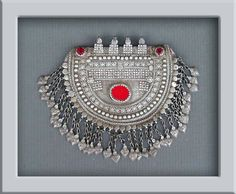 A collector's antique Bedouin crescent shape pectoral or necklace, from Arabian Peninsula. Early to mid 20th century. Excellent alloy of silver, decorated with red cut stones and plastic ( at the center ). Certainly made by a master jewish silversmith.
