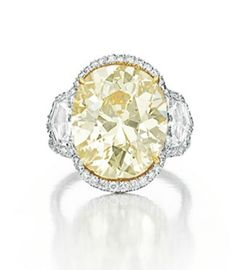A COLORED DIAMOND RING   Set with an oval-cut fancy brownish yellow diamond, weighing approximately 10.15 carats, flanked on either side by an epaulette-cut diamond, to the circular-cut diamond surround and shoulders, the gallery decorated with circular-cut diamond and yellow diamond detail, mounted in gold and platinum