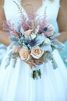 The gorgeous bouquet was made of peach and cream roses, dusty miller, blue thistle and pink astibile. Florist: Two Lemons in Love